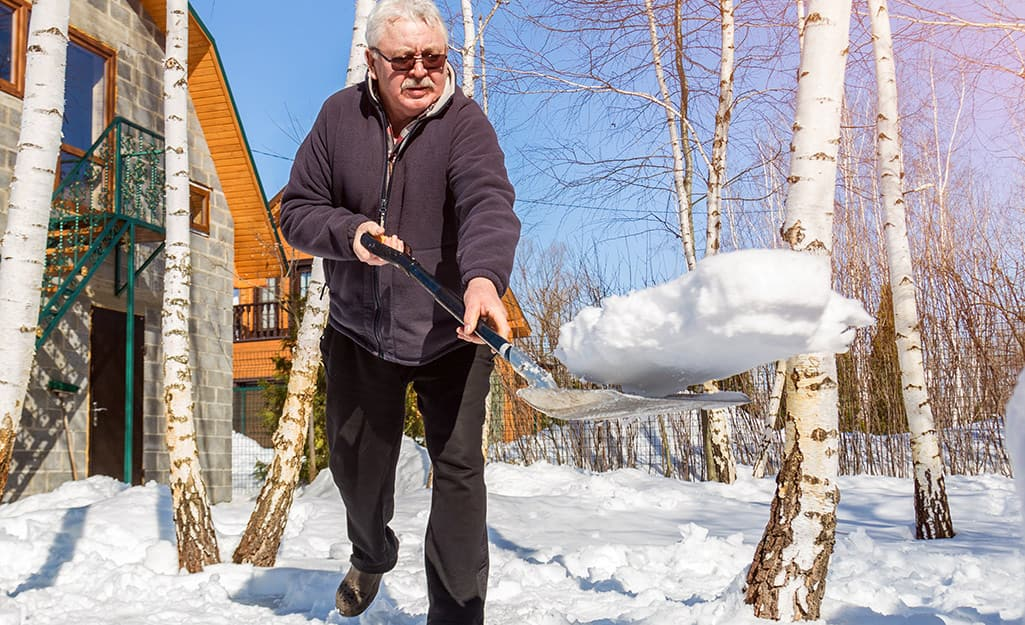 A person tossing a scoop of snow from a snow shovel.