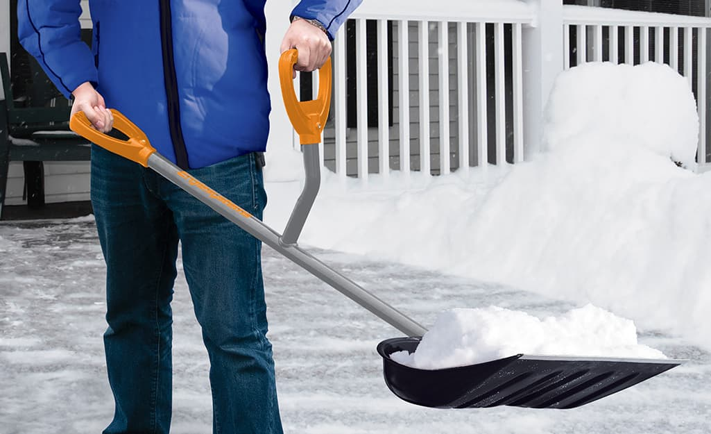 A person holding a snow shovel with an ergonomic handle.