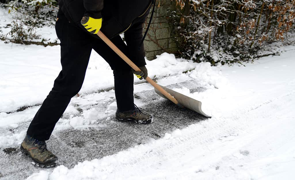 A person using a snow shovel to remove snow from a driveway.