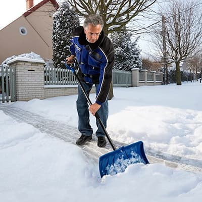 A person shoveling snow in a driveway.
