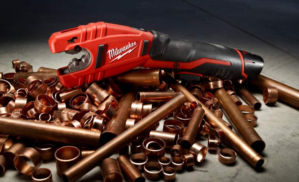 A pipe cutter sits atop a pile of copper pipe and copper pipe fittings.