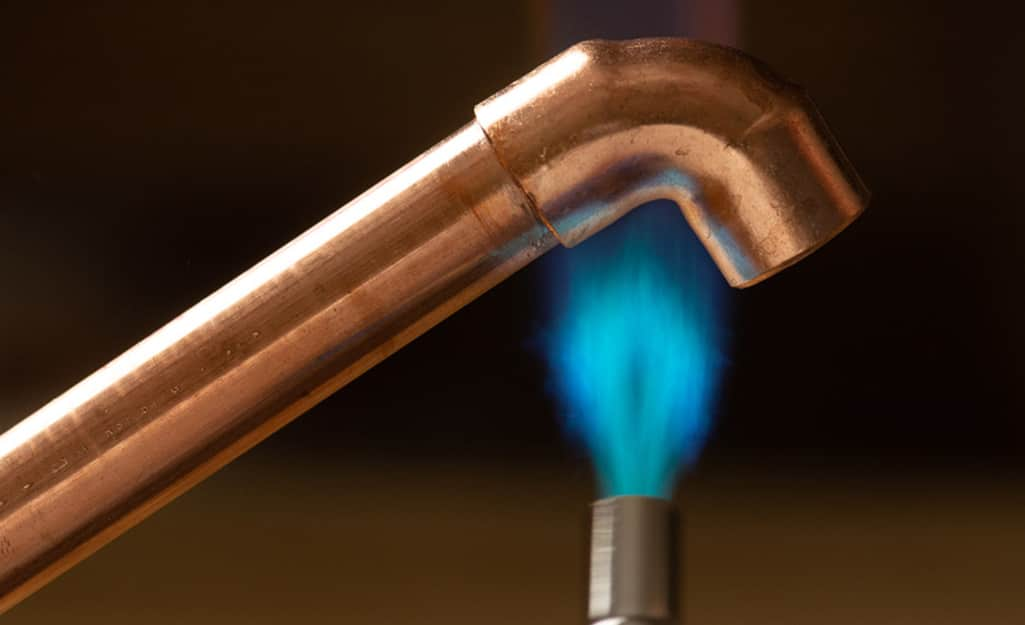 A soldering iron flame heats a copper fitting.