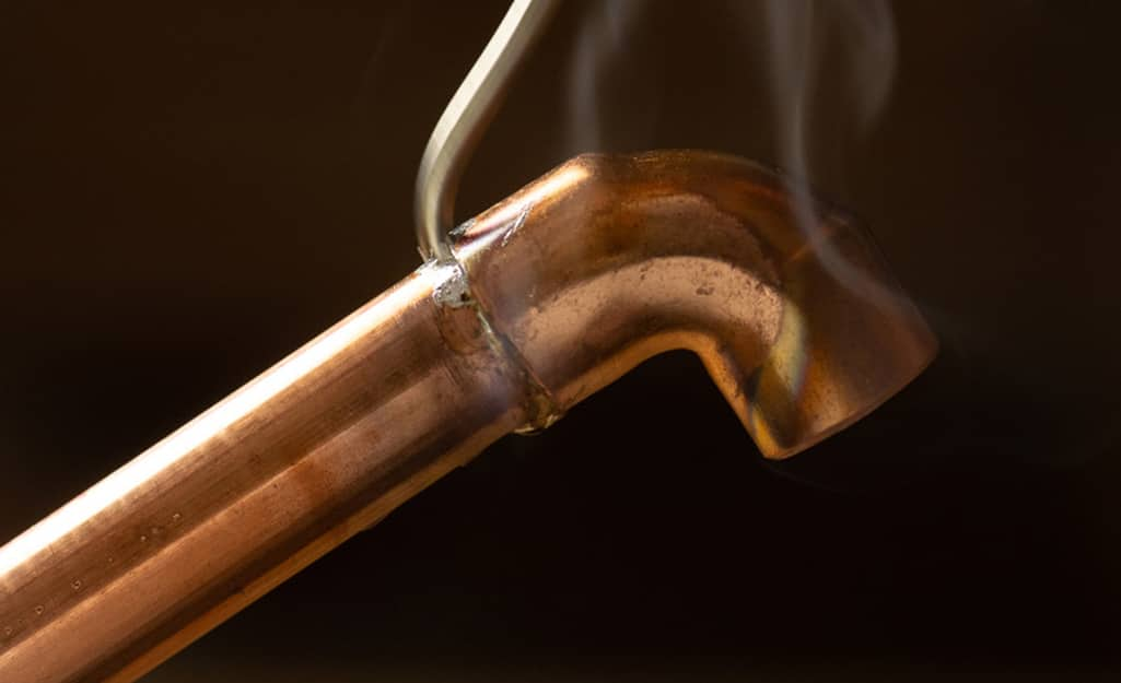 Someone applying solder to the joint between a copper fitting and pipe.