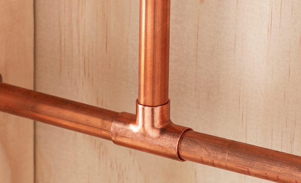 Two copper pipes joined with a tee fitting.