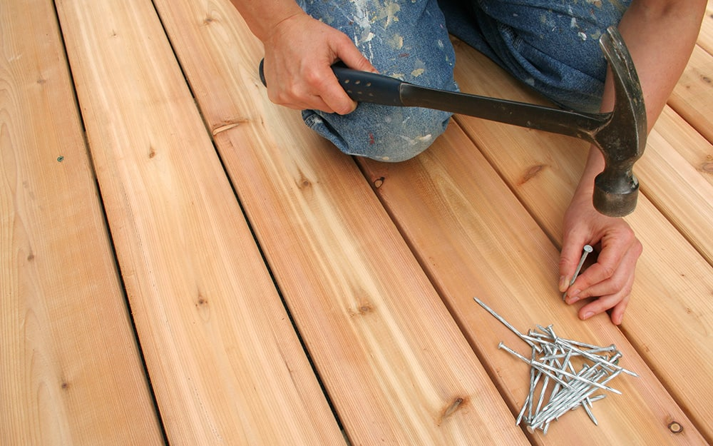 A person hammers a nail into a deck board.