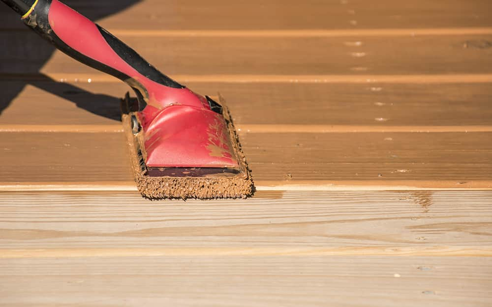 A person stains deck boards with a pad applicator.