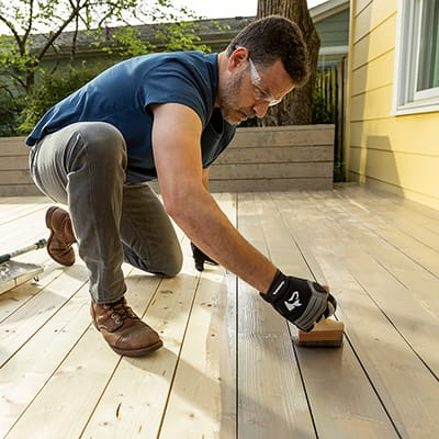 A man stains deck boards with a brush.