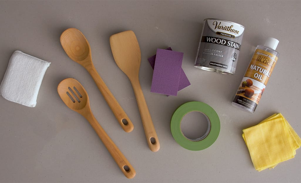 Wooden utensil set, stain, sandpaper and other supplies gathered together.