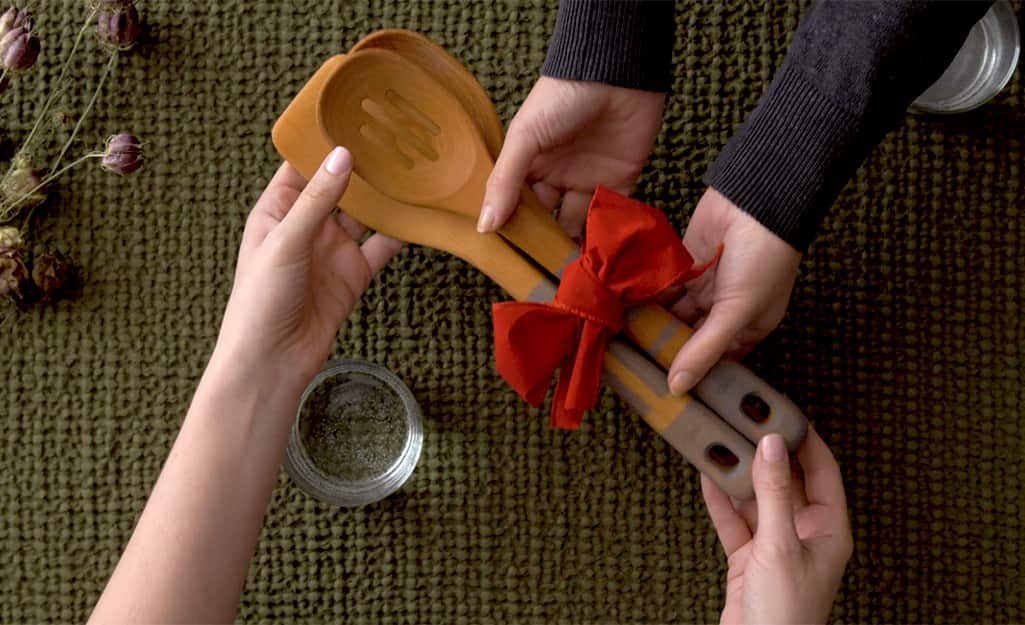 The spoons are wrapped in a red bow and given as a gift.