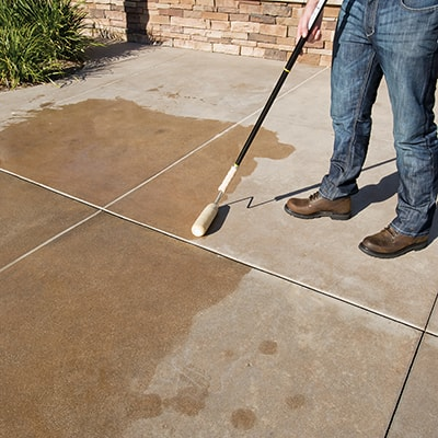 A person using a roller to dampen a concrete slab.