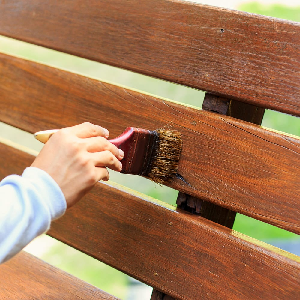 A person uses a brush to stain a bench made of pressure-treated wood.