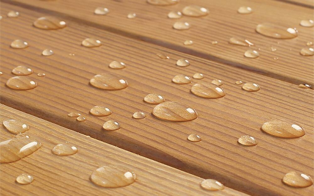 Water droplets bead on a pressure-treated wood surface.