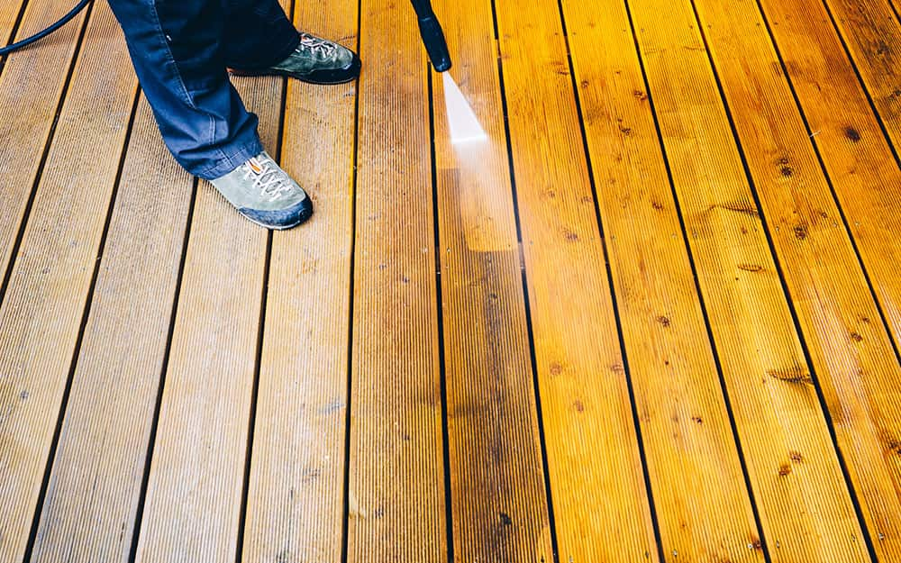 A person washes a pressure-treated wood deck with a sprayer.