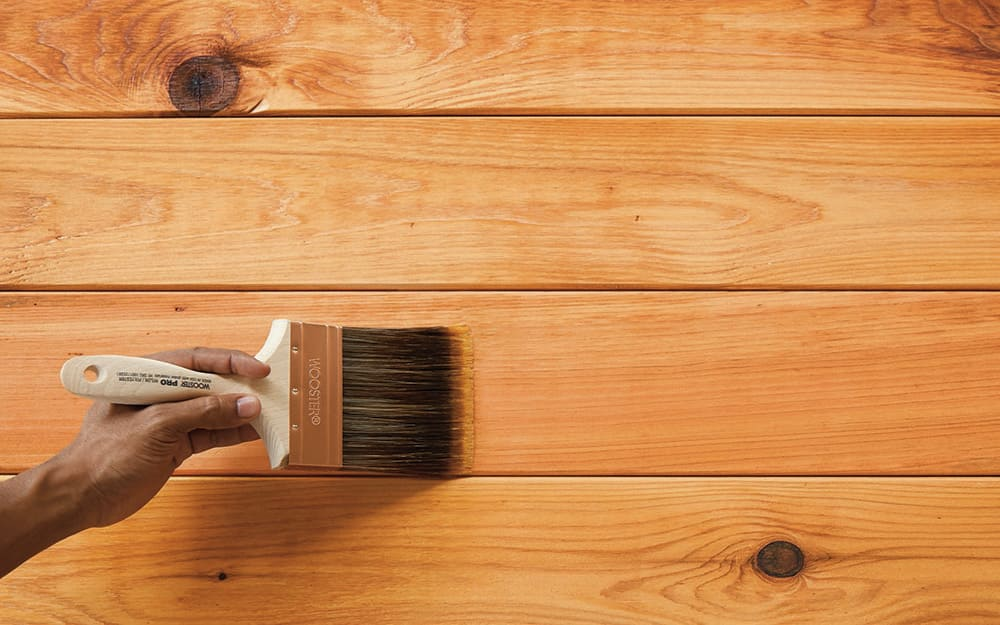 A person applies sealant to a pressure-treated wood surface with a brush.