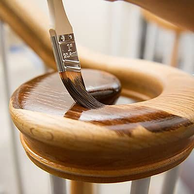 A brush applies stain to a wooden handrail.
