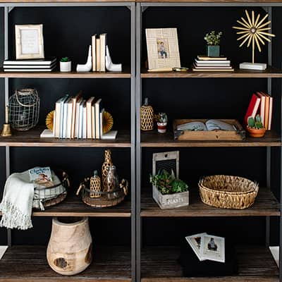 Two industrial style open bookcases styled with a variety of books and decor.