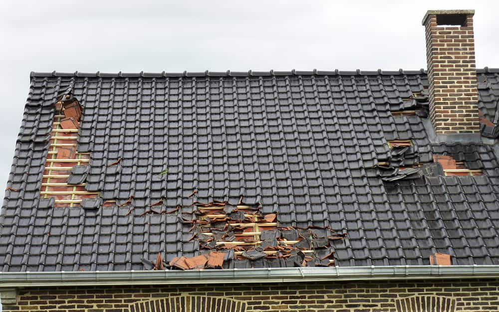 a roof with damage to the shingles in multiple areas