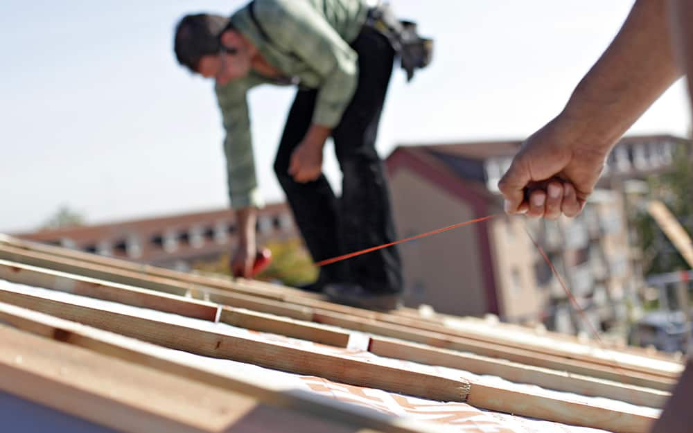 two people using a laser distance measure to measure a roof