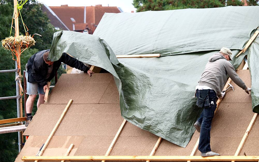 two people covering a roof with a large piece of tarp