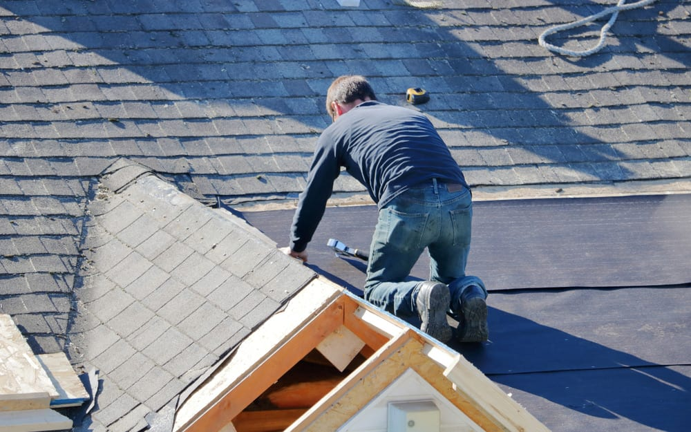 a man securing a tarp to a section of a roof