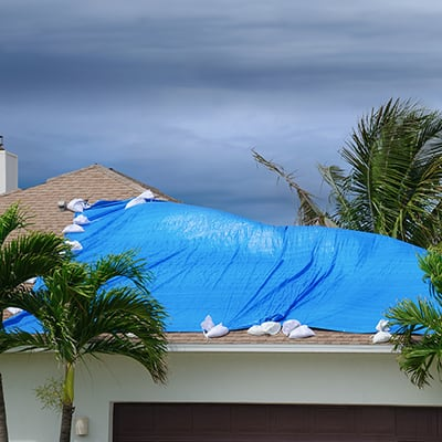 a roof partially covered by a blue tarp