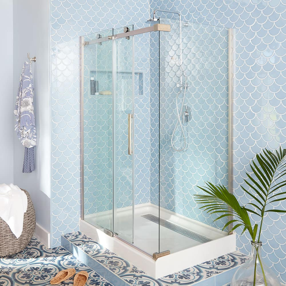 A bathroom with blue and white shower tile.