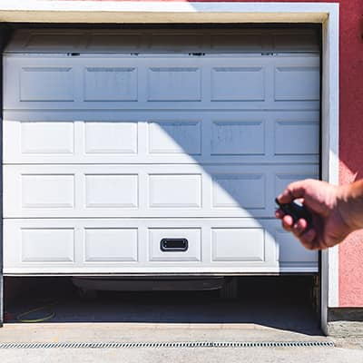 A person uses a remote control to open a garage door.