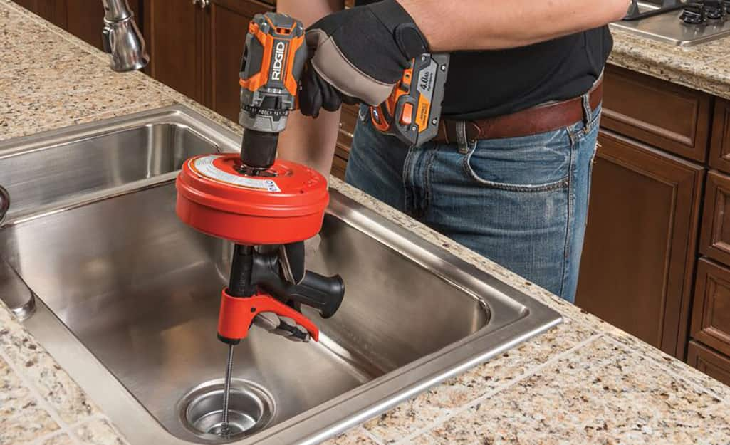 A person uses an auger on the upper part of a kitchen sink.