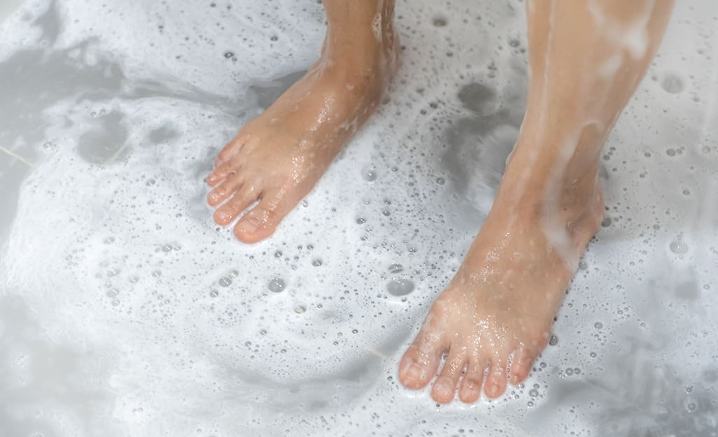 Sudsy water surrounds a person's bare feet