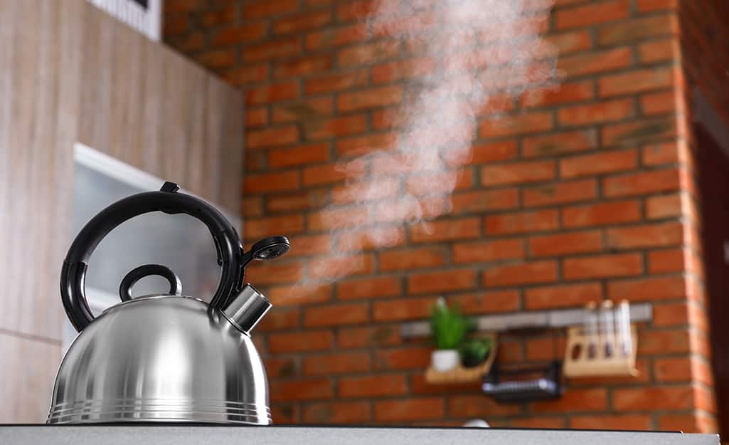 A silver kettle boils on a stove and its steam is visible against a brick wall