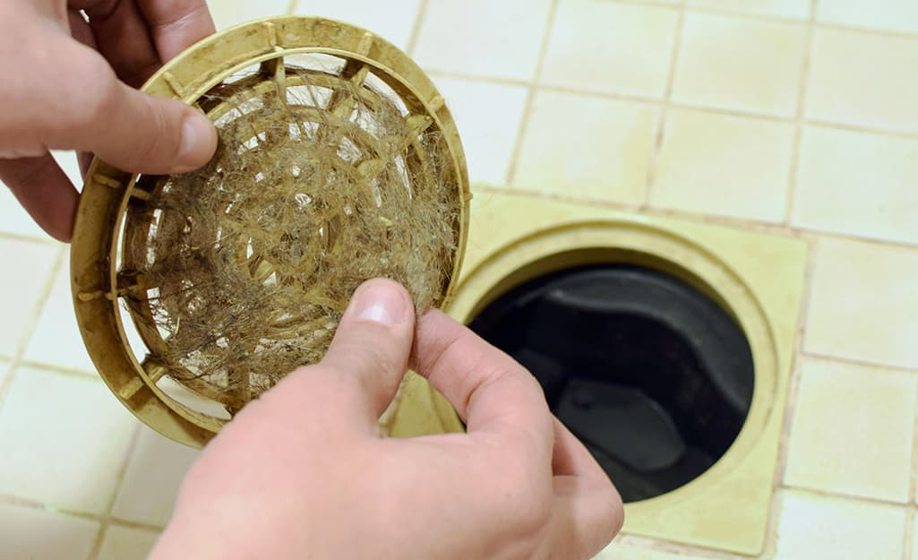 A person uses their fingers to pick hair off the cover of a clogged shower drain