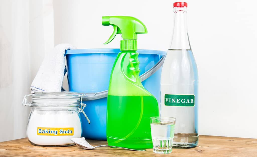 A container of baking soda sits next to a blue bucket, a green spray bottle and a bottle of vinegar