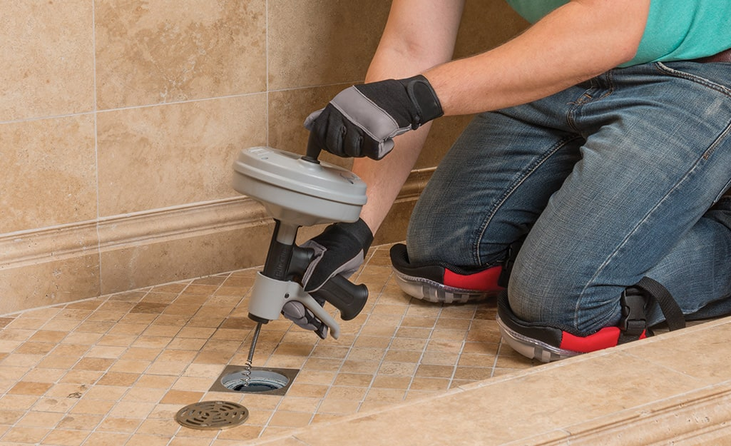 A person wearing knee pads kneels in a shower as they use a plumber's snake to unclog a shower drain