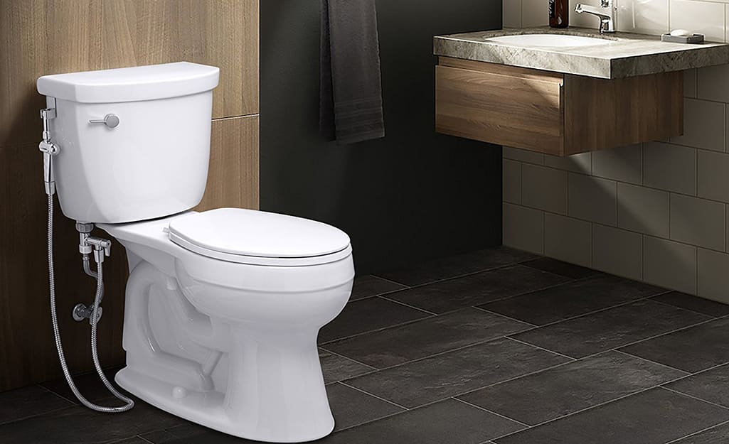A hand-held bidet sprayer is installed on the side of a toilet in a bathroom.