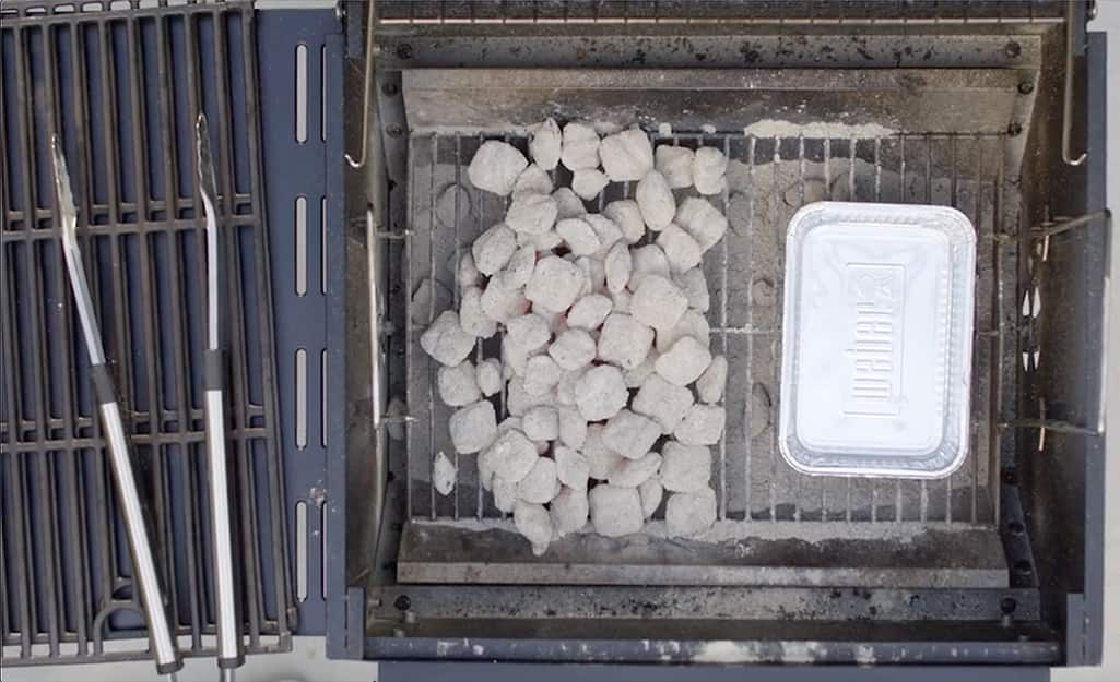 Coals in a charcoal grill arranged for two-zone cooking.