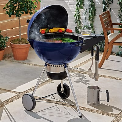 A blue kettle grill cooking food on a patio.
