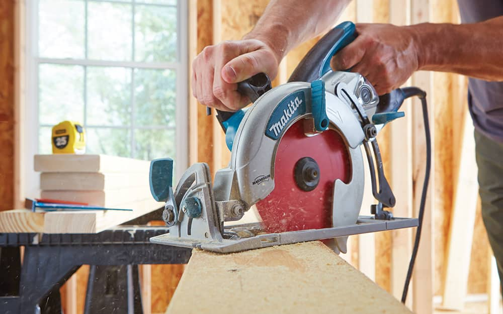 Person sawing a board with a circular saw.