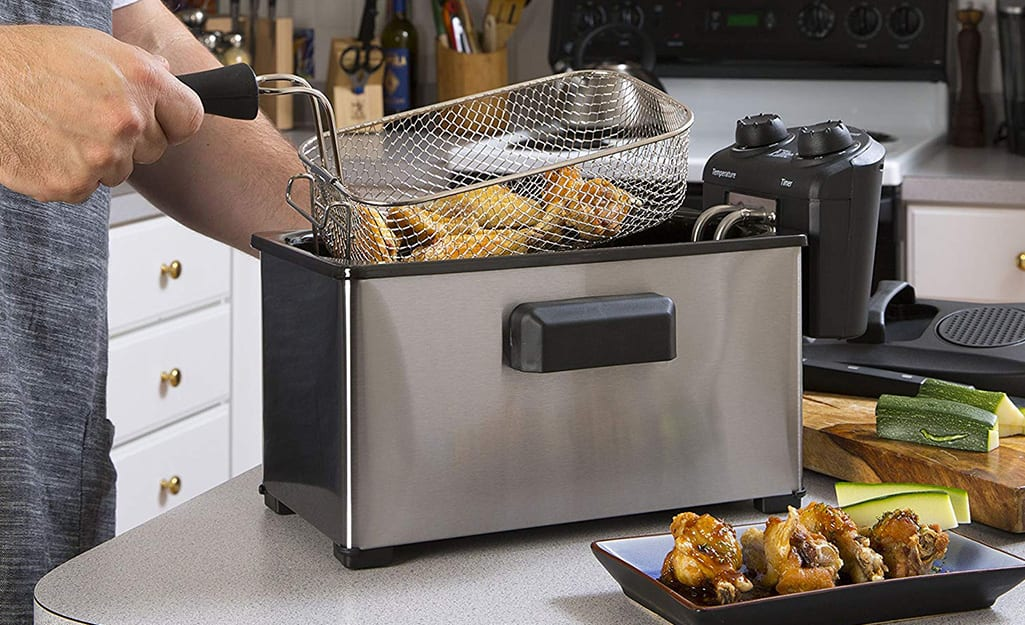 Some removing a basket of fried food from a countertop deep fryer.