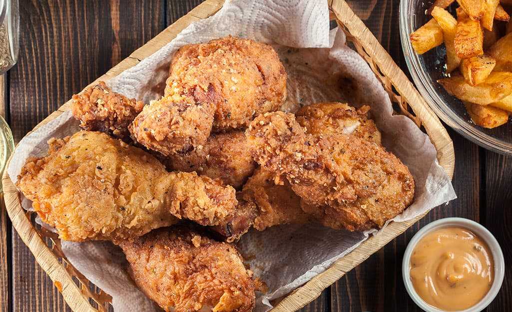 Pieces of fried chicken cooked in a deep fryer draining on paper towels.