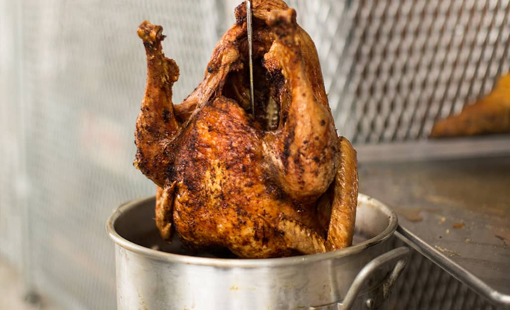 Someone lifting a fried turkey out of an outdoor turkey fryer.