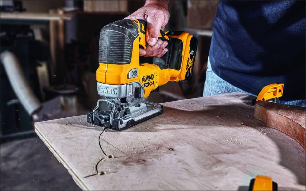 A jigsaw cutting along a curved line on a board.