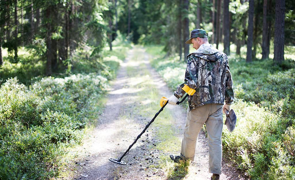 A person using a metal detector in a wooded area.