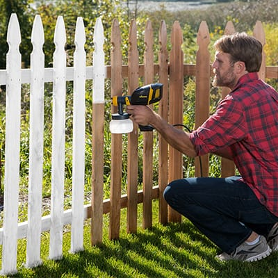 Man in plaid shirt paints a picket fence white with a paint sprayer.
