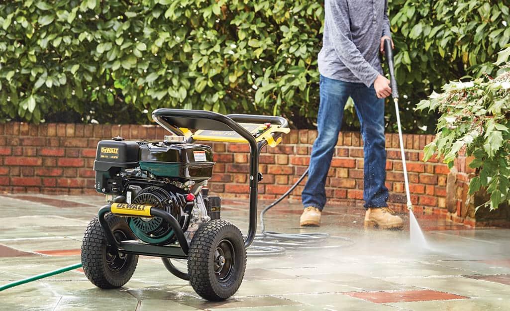 A man pressure washes his sidewalk.