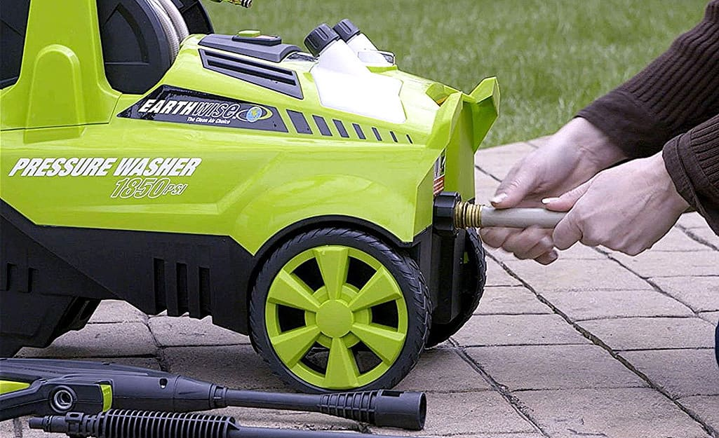 A person removes a garden hose from the pressure washer's water inlet.