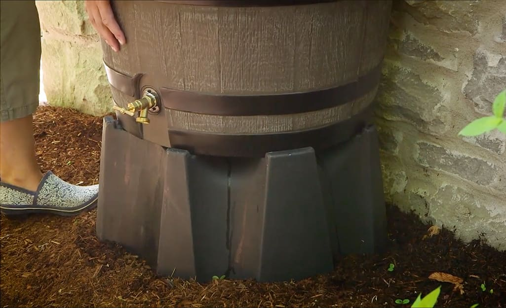 A rain barrel is placed on a raised stand to improve water flow.