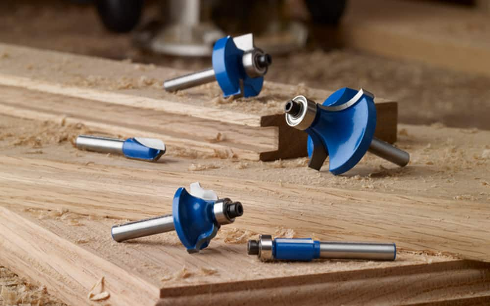 A set of router bits on a wood surface.