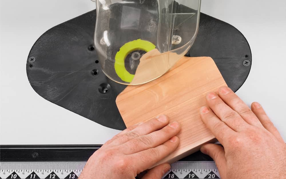 A person rounding wood edges with a router.