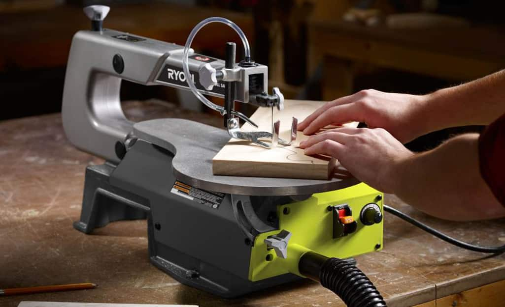 A person using a scroll saw to cut a wooden board.