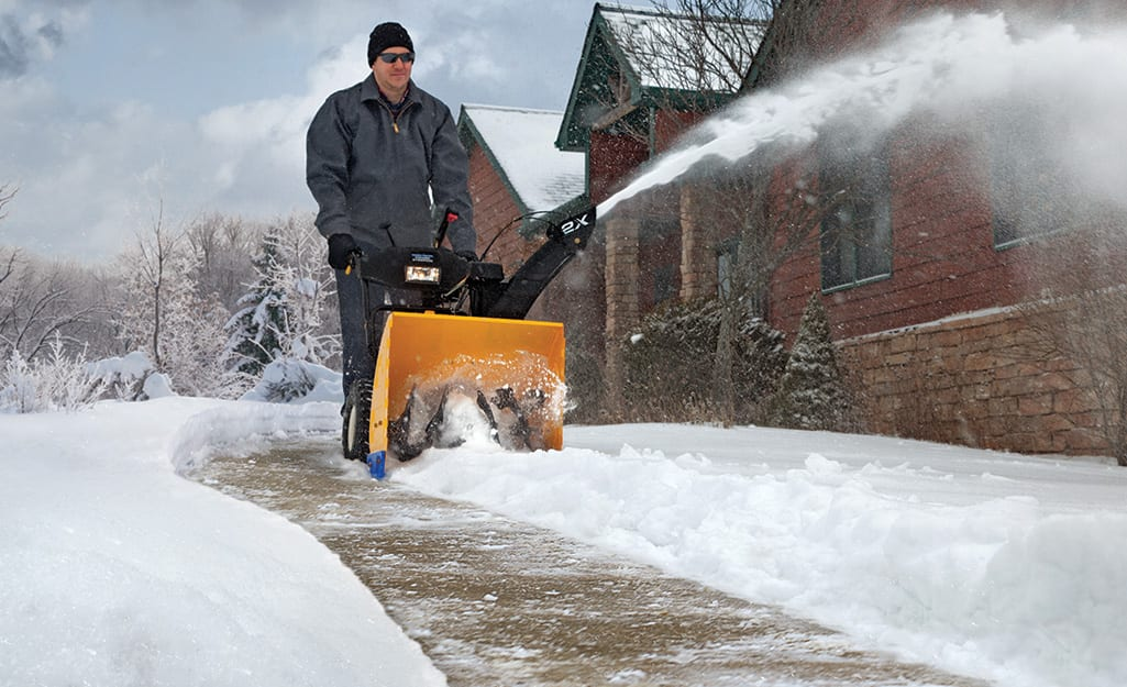 A person using a snow blower to clear snow from a sidewalk.